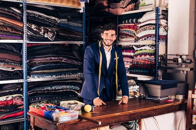 Portret van een glimlachende jonge mannelijke manierontwerper die camera in zijn winkel bekijkt