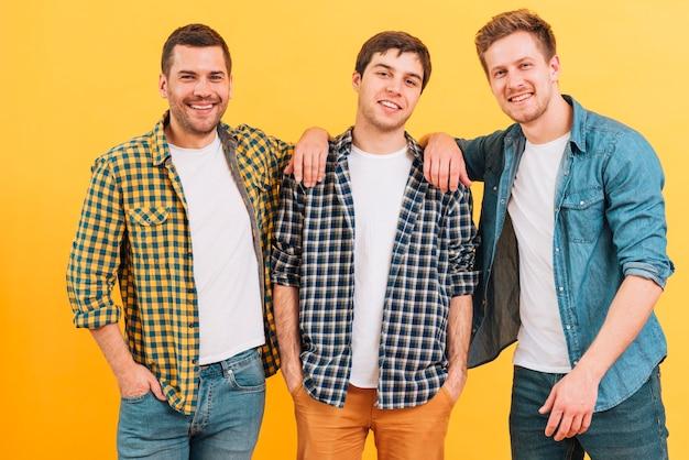 Portret van een glimlachende jonge mannelijke vriend die zich tegen gele achtergrond bevindt