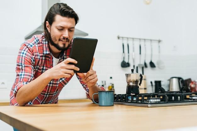Portret van een glimlachende jonge mens die op houten keukenteller leunt die slimme telefoon bekijkt
