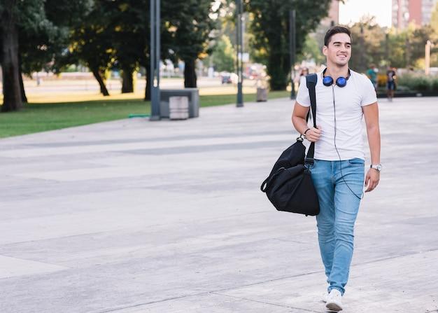Portret van een glimlachende jonge mens die op straat loopt