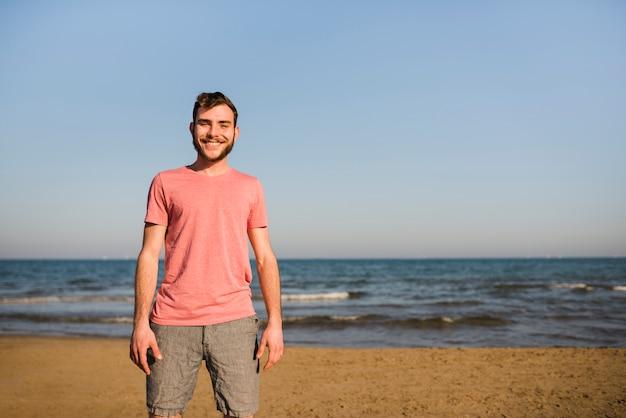 Portret van een glimlachende jonge mens die zich op het strand tegen blauwe hemel bevindt