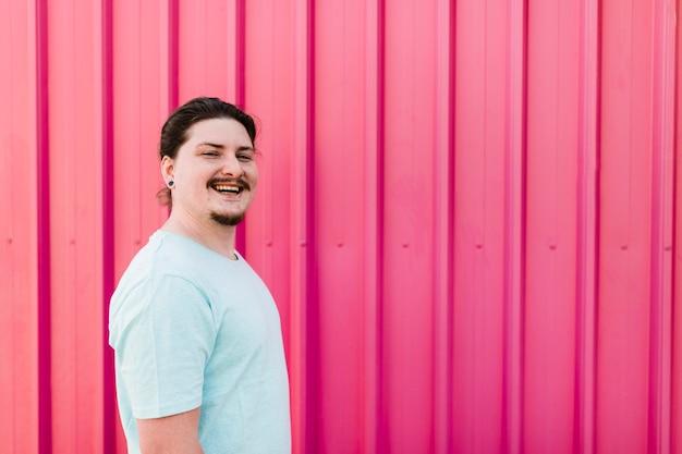 Portret van een glimlachende jonge mens die zich tegen roze golfmetaalblad bevindt