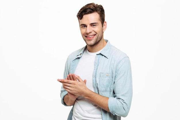 Portret van een glimlachende jonge mens die zijn handen wrijft