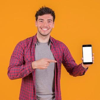 Portret van een glimlachende jonge mens die zijn mobiele telefoon toont tegen een oranje achtergrond