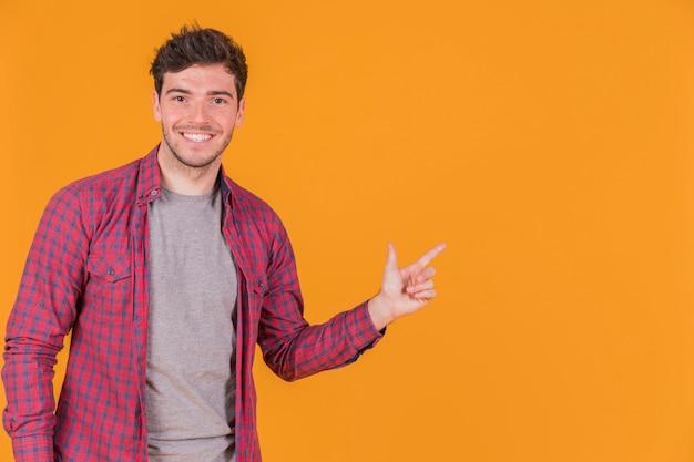 Portret van een glimlachende jonge mens die zijn vinger op een oranje achtergrond richt