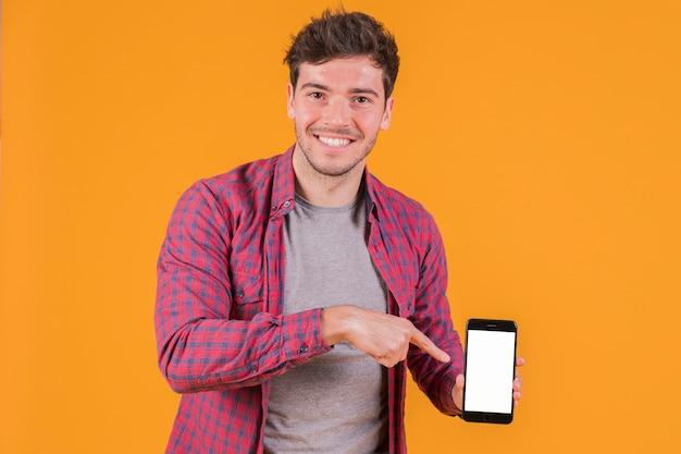 Portret van een glimlachende jonge mens die zijn vinger op mobiele telefoon richt tegen een oranje achtergrond