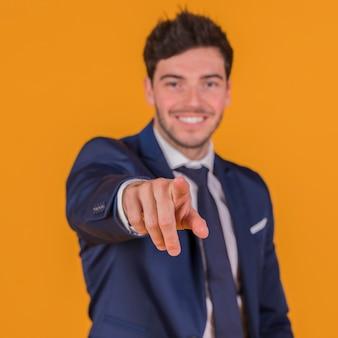 Portret van een glimlachende jonge mens die zijn vinger richt tegen een oranje achtergrond