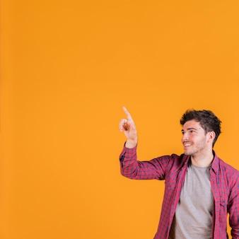Portret van een glimlachende jonge mens die zijn vinger richt tegen oranje achtergrond