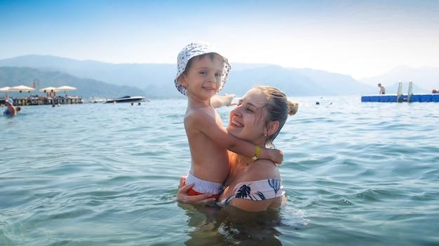 Portret van een glimlachende jonge moeder die in zee staat en haar zoontje peuter vasthoudt.