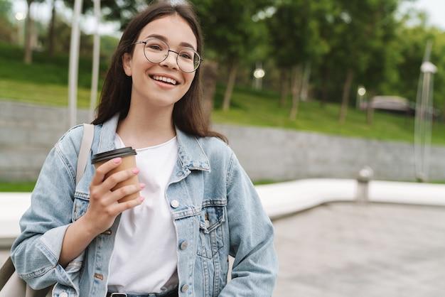 Portret van een glimlachende jonge, mooie studente die buiten in het groene natuurpark koffie drinkt