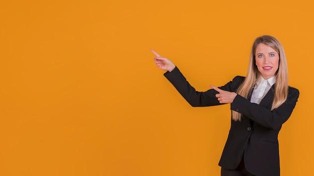 Portret van een glimlachende jonge onderneemster die iets voorstelt tegen een oranje achtergrond