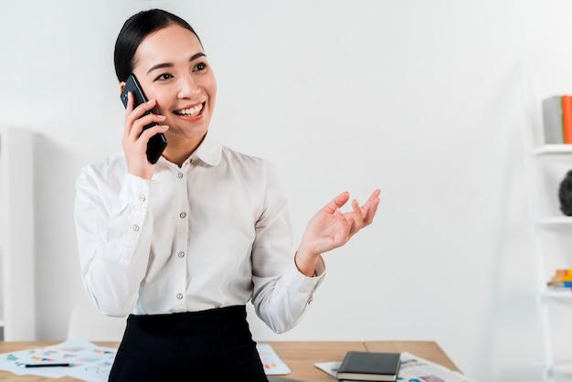 Portret van een glimlachende jonge onderneemster die op mobiele telefoon in het bureau spreekt