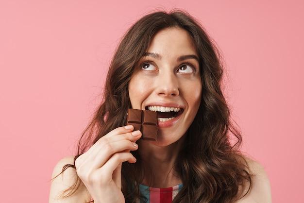 Portret van een glimlachende jonge, schattige vrouw die zich geïsoleerd over een roze muur voordeed en chocoladesnoepjes vasthoudt die dromen en opzij kijken