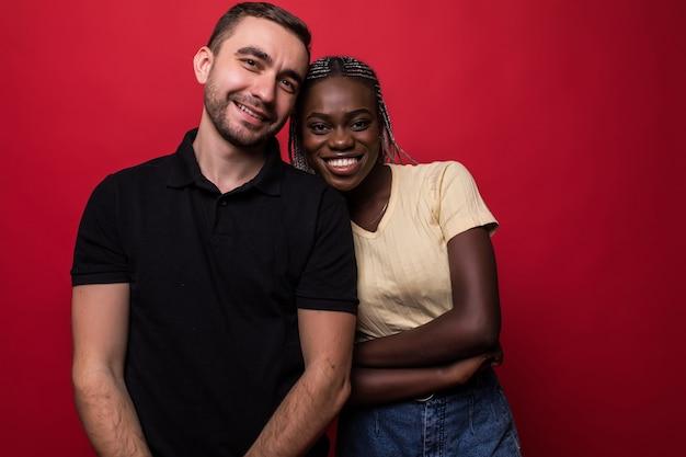 Portret van een glimlachende jonge sex tussen verschillendre rassen paar knuffelen en kijken naar camera geïsoleerd op de rode achtergrond