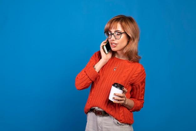 Portret van een glimlachende jonge toevallige vrouw die op mobiele telefoon spreekt die over blauwe achtergrond wordt geïsoleerd.