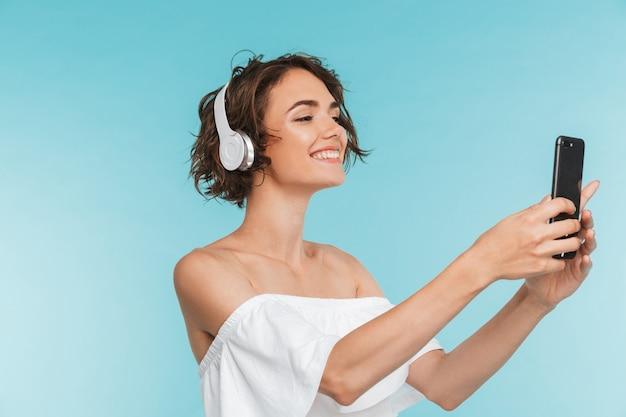 Portret van een glimlachende jonge vrouw die aan muziek luistert