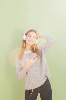 Portret van een glimlachende jonge vrouw die de muziek op hoofdtelefoon tegen munt groene achtergrond luistert