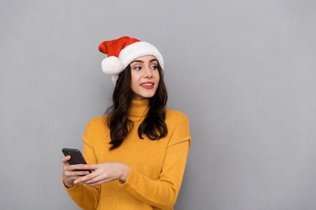 Portret van een glimlachende jonge vrouw die de rode hoed van de kerstman draagt die zich geïsoleerd over grijze achtergrond bevindt, die mobiele telefoon gebruikt