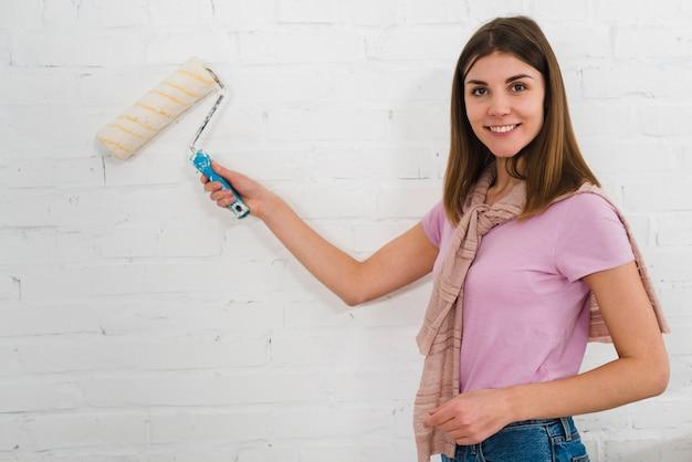 Portret van een glimlachende jonge vrouw die de verfrol op witte bakstenen muur met behulp van