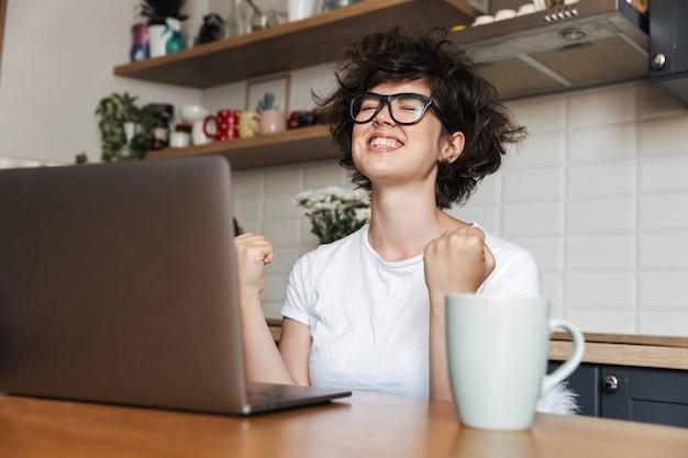 Portret van een glimlachende jonge vrouw die een bril draagt die op laptop computer thuis werkt in de ochtend, viert