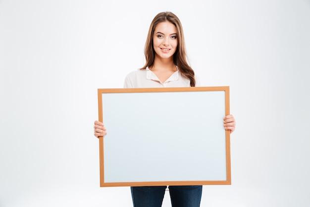 Portret van een glimlachende jonge vrouw die een leeg bord toont dat op een witte muur wordt geïsoleerd