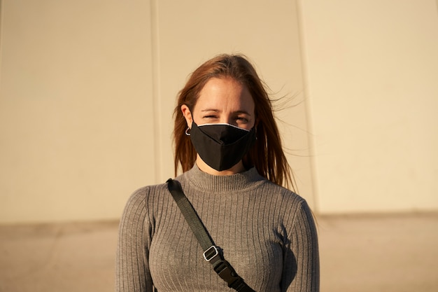 Portret van een glimlachende jonge vrouw die een masker draagt vanwege de pandemie van het coronavirus