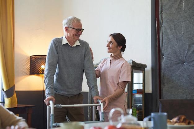 Portret van een glimlachende jonge vrouw die een oudere man helpt met een rollator in de kopieerruimte van een verpleeghuis