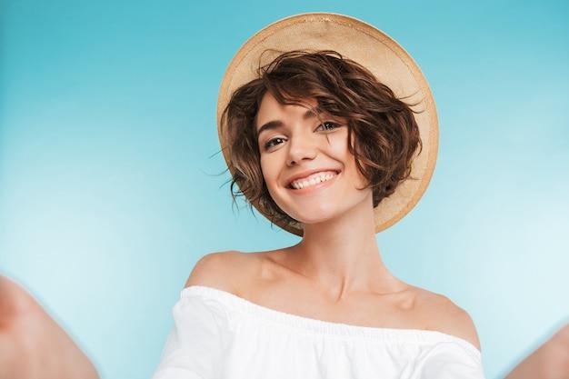 Portret van een glimlachende jonge vrouw die een selfie neemt