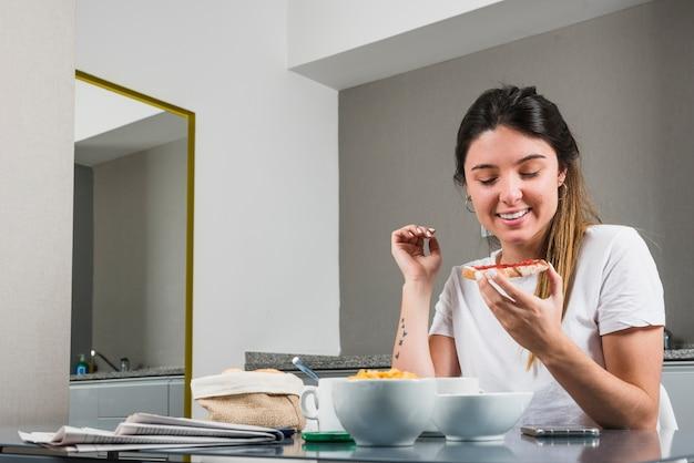 Portret van een glimlachende jonge vrouw die gezond ontbijt thuis eet