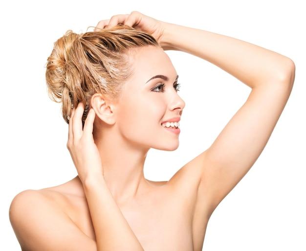 Portret van een glimlachende jonge vrouw die haar haar op een witte muur wast
