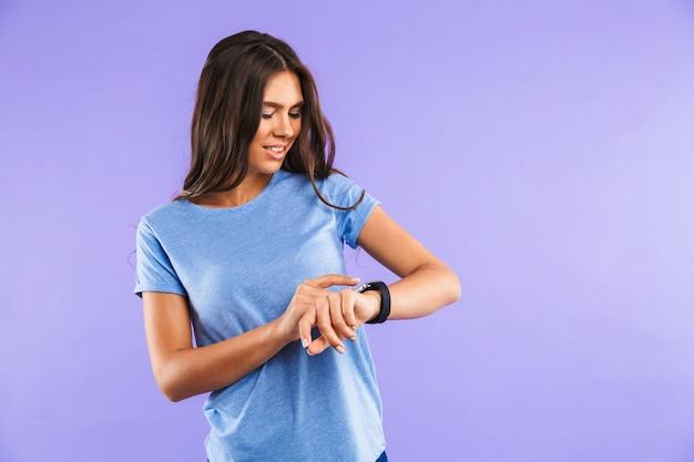 Portret van een glimlachende jonge vrouw die haar smartwatch bekijkt