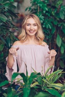 Portret van een glimlachende jonge vrouw die haar vinger naar beneden naar groene houseplant richt