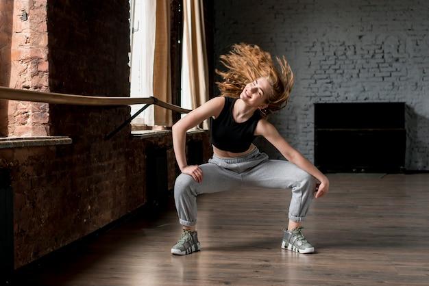 Portret van een glimlachende jonge vrouw die in de studio danst