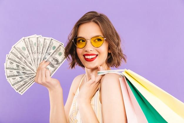 Portret van een glimlachende jonge vrouw die in zonnebril het winkelen zakken en geldbankbiljetten houden