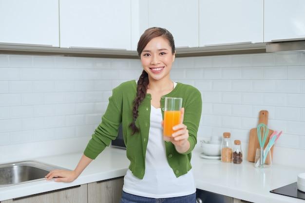 Portret van een glimlachende jonge vrouw die sinaasappelsap in de keuken thuis drinkt