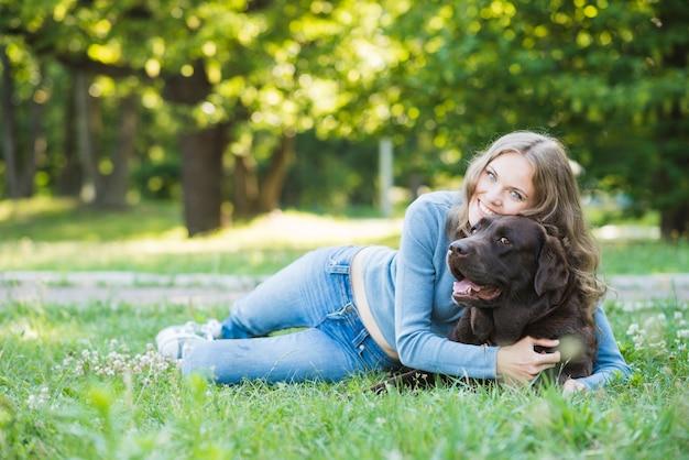 Portret van een glimlachende jonge vrouw die van haar hond in tuin houden