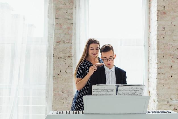 Portret van een glimlachende jonge vrouw die zich achter de man spelen piano in de buurt van het venster