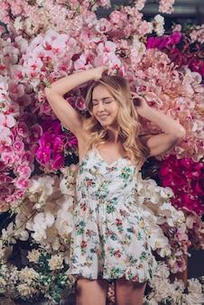 Portret van een glimlachende jonge vrouw die zich voor plastic orchideebloemen bevindt