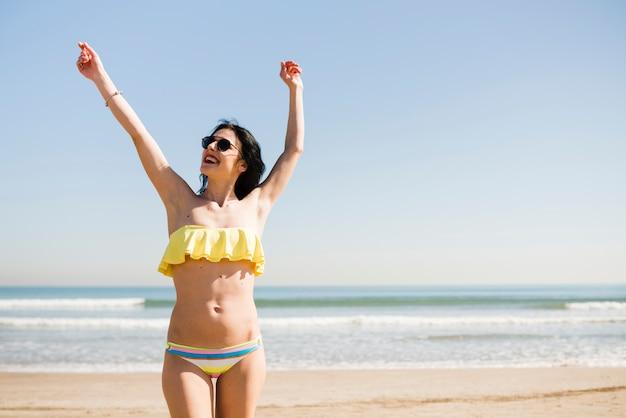 Portret van een glimlachende jonge vrouw in bikini die zich dichtbij het overzees tegen blauwe hemel bij strand bevinden