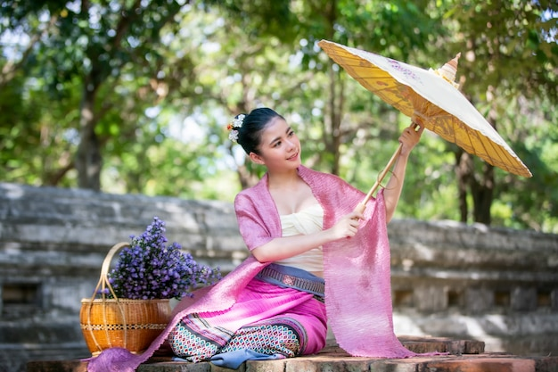 Portret van een glimlachende jonge vrouw in de thaise paraplu van lanna traditional clothes holding