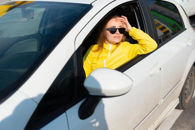 Portret van een glimlachende jonge vrouw in een gele jas die een zonnebril draagt en in haar auto zit