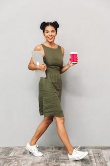 Portret van een glimlachende jonge vrouw in geïsoleerde kleding, die laptop en afhaalkoffie draagt, het lopen