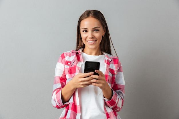 Portret van een glimlachende jonge vrouw in geruite overhemd