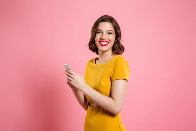 Portret van een glimlachende jonge vrouw in jurk