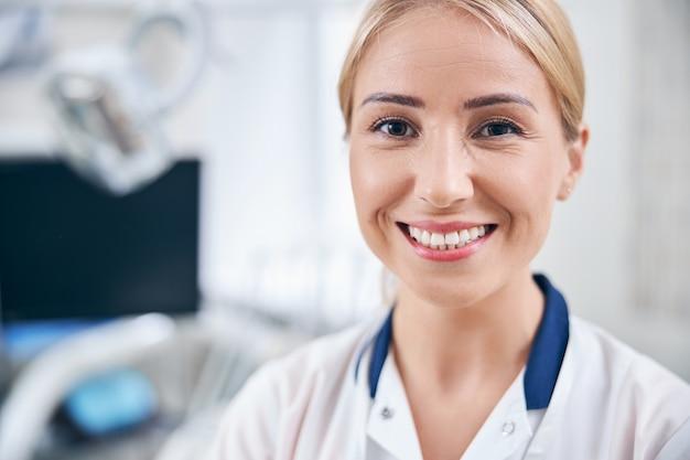 Portret van een glimlachende jonge vrouw in medisch uniform die in de buurt van moderne apparatuur in het kantoor van de kliniek staat