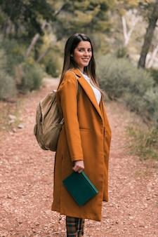 Portret van een glimlachende jonge vrouw met boek van de rugzakholding ter beschikking
