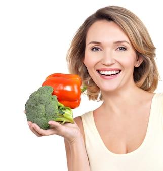 Portret van een glimlachende jonge vrouw met groenten die op wit wordt geïsoleerd.