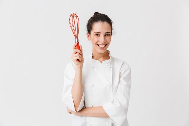 Portret van een glimlachende jonge vrouw met keukengerei