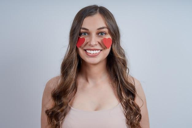 Portret van een glimlachende jonge vrouw met rode harten die aan haar wangen worden geplakt. fijne valentijnsdag.