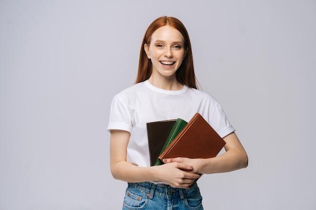 Portret van een glimlachende jonge vrouwelijke student die een boek vasthoudt en naar de camera kijkt